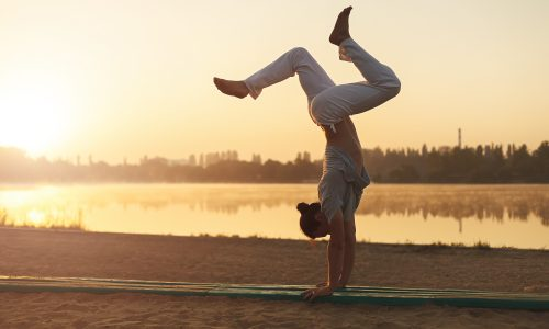 Concept about lifestyle and sport. Capoeira on the beach, near lake one performer, at sunrise. Athletic man in white pants standing on arms upside down while workout in the park in the heart of city.